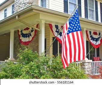 The front porch of a patriotic bed and breakfast inn in Oklahoma is proudly festooned with an American flag and banners.