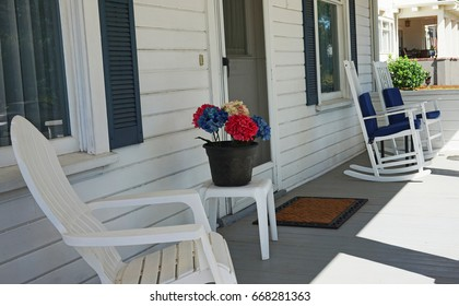 A Front Porch With Patriotic Decorations.  White rocking chairs with blue pads in the shade looks very inviting on a hot summer day.