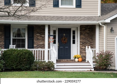 Front porch of suburban home decorate for fall holidays