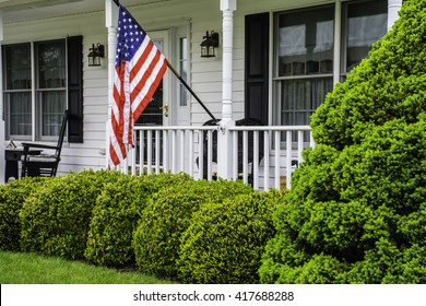front porch of white colonial home with black shutters and rockers flying the American flag