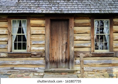Front porch and windows of a historical pioneer log cabin. Pt. Sanilac Historical Village. Pt. Sanilac, Michigan.