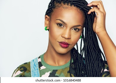 Front portrait of beautiful African-American woman model with accurate black dreadlocks and make-up, with her hand to her hair, wearing green camouflage shirt