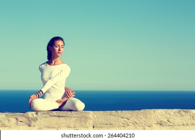 Front portrait of gorgeous young woman practicing yoga on a sunny day with amazing sea horizon on background, woman seeking enlightenment through meditation,relaxed girl performing yoga routine,filter