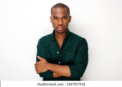 Front portrait of handsome young black man against isolated white background with arms crossed