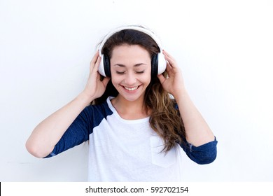 Front portrait of happy young woman holding headphones and listening to music