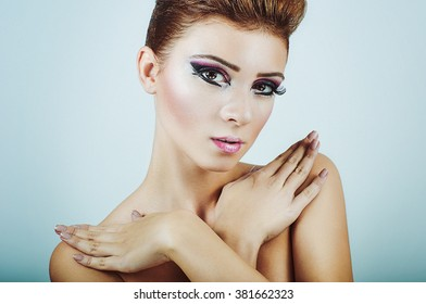 Front portrait of a nude girl with beautiful make-up and arms crossed over chest