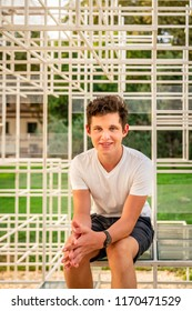 Front portrait of a smiling teenage boy sitting on a abstract art steel frame outdoors.