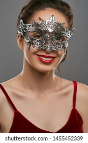 Front portrait of smiling woman with tied back dark hair, wearing wine red crop top. The young girl is tilting head, wearing silver opalesce carnival mask with fancy perforation and jutting edges.