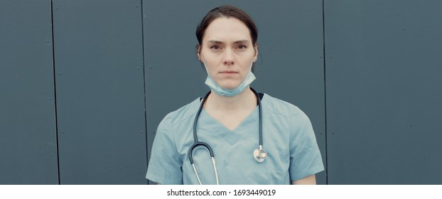 FRONT Portrait of tired nurse or doctor wearing medical mask looking into camera. COVID-19, Coronavirus pandemic