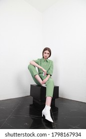 Front portrait of woman with slicked down hair, wearing cotton summer light green suit. The girl is sitting on the black cube and looking to camera on white background,  - Shutterstock ID 1798167934