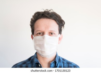 Front portrait of a young man wearing a disposable face mask, to prevent the spread of the coronavirus disease, Covid-19