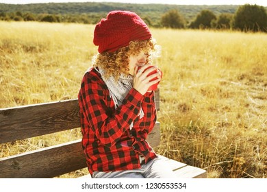 Front portrait of a young woman in red plaid shirt with a wool cap and scarf taking a cup of tea or coffee while she is sunbathing sitting in a yellow field with backlight from autumn sun
