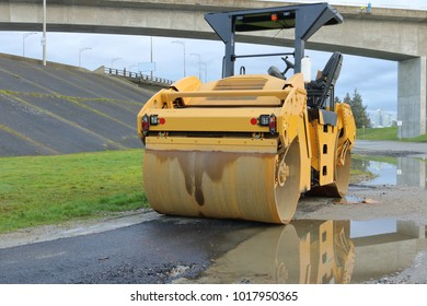 Front profile view of a heavy duty industrial roller compactor used for smoothing surfaces that have had asphalt applied for road construction.
