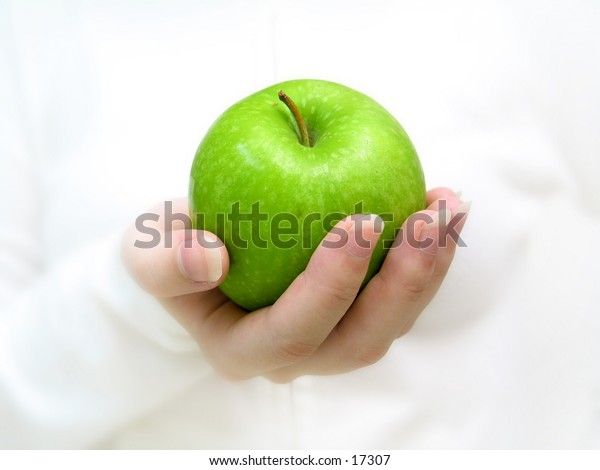 Front profile of a woman holding a green apple in her hands.