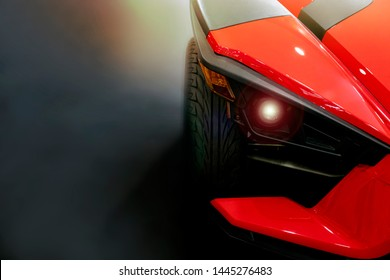 Front of red color sport car on black background.
