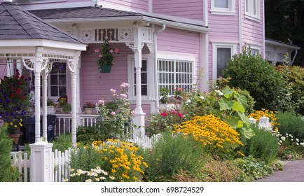 Front of a restored Victorian home with a garden of summer flowers