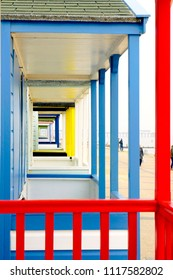 The front of a row of colourful beach huts in Southwold, UK