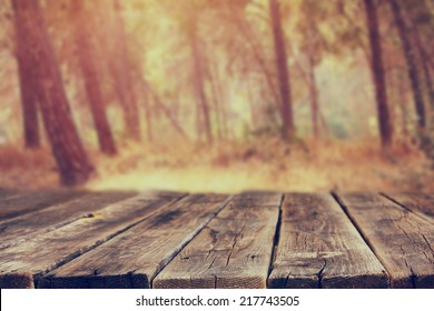 front rustic wood boards and background of trees in forest. image is retro toned
