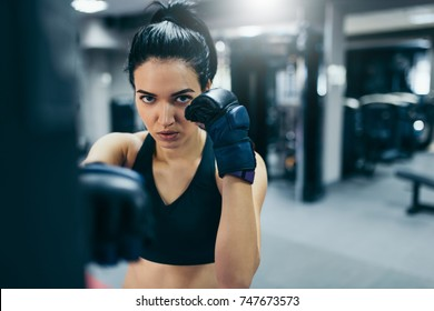 Front shot of attractive brunette woman punching a bag with kickboxing gloves in the gym workout. Sport, fitness, lifestyle and people concept.