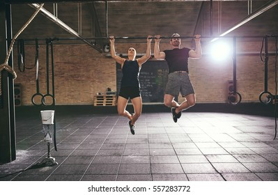 Front shot of two young athletic people dowing pull-ups together in spacious light gym.