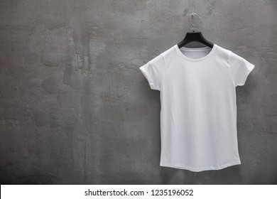 Front side of female white cotton t-shirt on a hanger and a concrete wall in the background. T-shirt without print and copyspace for your text on left side