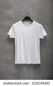 Front side of male white cotton t-shirt on a hanger and a concrete wall in the background. T-shirt without print
