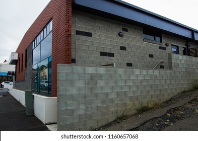 The front and side of a modern commercial building bordered by a torn road and bland brickwork on a commercial city street.
