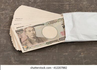 in front side of ten thousand yen japanese money in white  envelope on table