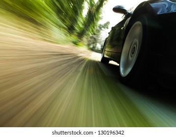 Front side view of black car driving fast.