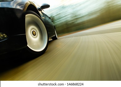 Front side view of black car in turn with heavy blurred motion.