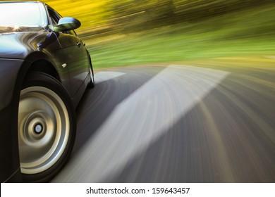 Front side view of black sedan in turn.
