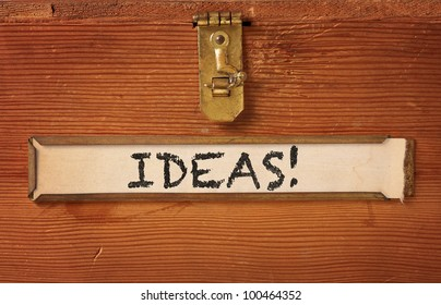 "The front of a simple wooden box featuring a brass latch and label holder. ""Ideas"" is hand written on the yellowing label."