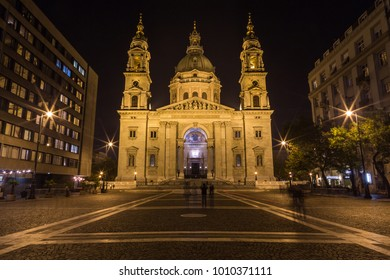The the front of St. Stephen's Basilica in Budapest at night from the street. The blur of people can be seen.