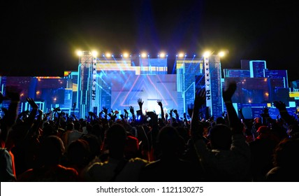 Front stage of music concert, frontal lights and lazer projection. Summer festival crowd. Light show and lazer projection. Crowd cheering and dancing.