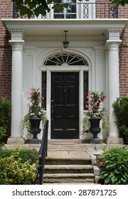 front steps of brick house with portico entrance and pink amaryllis