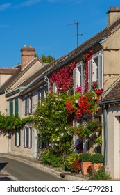 The front of this welcoming French home  is filled with flower boxes and planters, including a rambling rose.