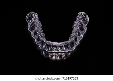 Front top view of a clear aligner or retainer of the lower teeth, used in orthodontic treatment for patients who wish for invisible braces to align their teeth, isolated against a black background.