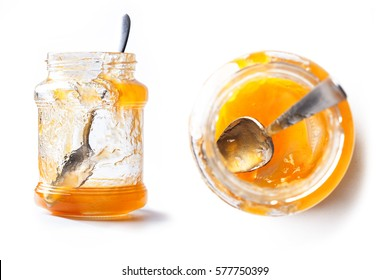 Front and top view of an empty pot of peach jam with spoon inside and white background