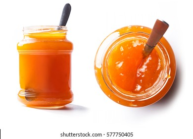 Front and top view of a pot of peach jam with spoon inside and white background