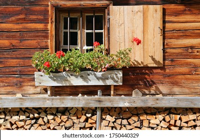 Front of a traditional wooden lodge with a window with a folding shutter and decorated with red blooming geraniums in a wooden flower box and fuelwood below- typical in the Bavarian or Austrian Alps