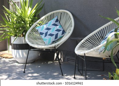 Front veranda of a house with two white Acapulco chairs and cushions - plant in a pot