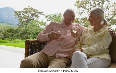 Front view of active senior Caucasian couple having champagne in the porch at home
