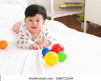 Front view of Adorable laughing boy baby on white bed sheet in a bedroom. Straight eye contact of innocent face in playing time. Baby laughing when playing colorful ball. innocent concept