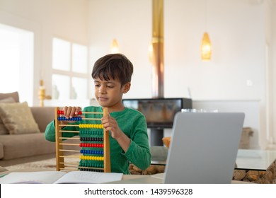 Front view of African american boy learning mathematics with abacus in a comfortable home