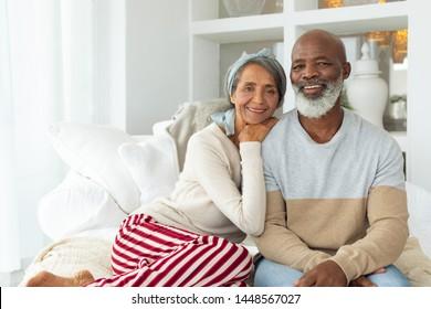 Vorderer Blick auf das Afroamerikanisches Paar, das in einem weißen Raum sitzt. Authentisches Konzept für das Leben im Senior