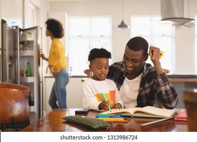 Front view of African American father helping his son with homework at table with mother opening the fridge on the background