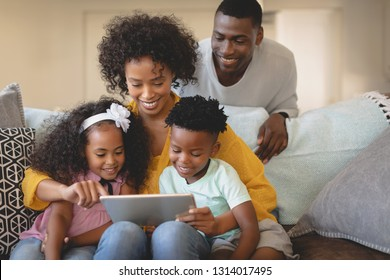 Front view of African American mother with her children using digital tablet on sofa while father looking at them in a comfortable home