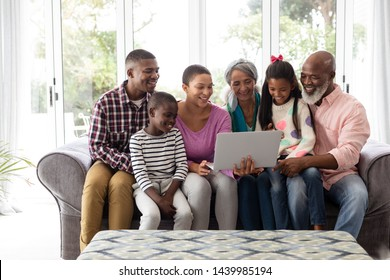 Front view of African american Multi-generation family using laptop on a sofa in living room at home