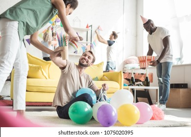 front view of african american woman and smiling young man on floor with balloons and their friends decorating room behind
