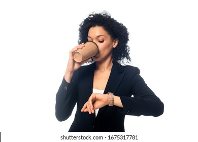 Front view of african american woman drinking coffee and looking at wristwatch isolated on white